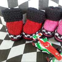 knitted baby booties with checkered flag motif and cuffs representing tires