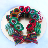 knitted christmas baby booties in a wreath shape