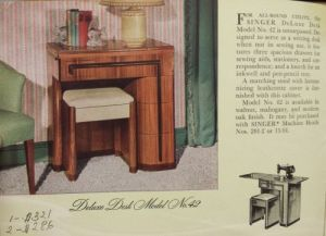 An old magazine advertisement for the Singer Deluxe Desk Model No. 42 wooden art deco-style sewing machine cabinet.