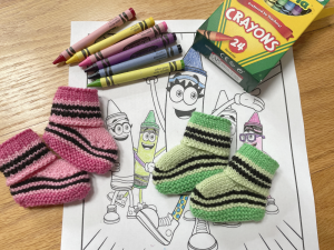 Two pairs of knitted baby booties made to look like crayons sit on a partially colored coloring sheet with a box of crayons and some loose crayons nearby.