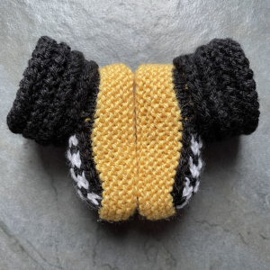A pair of yellow, black and white knitted booties with a cabled cuff made to look like a car tire sit sole to sole on a gray tile floor.